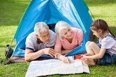 Деды при внучка обсуждая сверх Стоковое Изображение RF