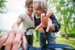 Деды смотря их внука в прогулочной коляске Стоковая Фотография