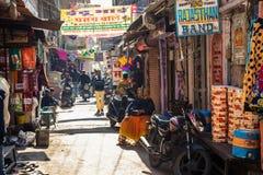 ДЖАЙПУР, ИНДИЯ - 10-ОЕ ЯНВАРЯ 2018: Традиционная улица Индии зима торговой операции улицы витрины ботинок теплая Стоковые Изображения