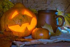 Джек-o-фонарик и глина mug с голубыми самыми интересными Стоковые Изображения