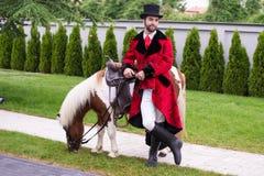 Джентльмен с верхней шляпой и его пони стоковое фото rf