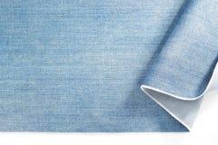 Джинсовая ткань голубых джинсов на белизне Стоковые Фотографии RF