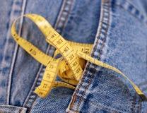 Джинсовая ткань голубых джинсов и желтая лента измерения Стоковые Изображения RF