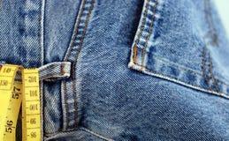 Джинсовая ткань голубых джинсов и желтая лента измерения Стоковая Фотография RF