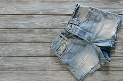 Джинсовая ткань одежды женщин замыкает накоротко на серой деревянной предпосылке с co Стоковое Изображение RF