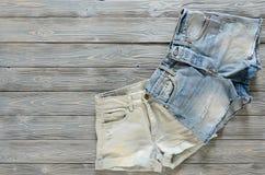 Джинсовая ткань одежды женщин замыкает накоротко на серой деревянной предпосылке с co Стоковые Фотографии RF