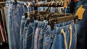 Джинсовые ткани вися на вешалках в магазине одежды готовом быть прода стоковые изображения rf