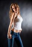 джинсыы девушки представляя белизну рубашки t Стоковое Изображение RF