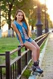Джинсыы девушки ролика нося сидя на загородке утюга Стоковое Изображение