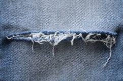 джинсыы джинсовой ткани предпосылки голубые сорванная деталь Текстура, конец вверх Стоковое Изображение