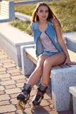Джинсыы девушки ролика нося сидя на стенде Стоковая Фотография RF