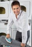 Джинсы бизнесмена утюжа в прачечной стоковые изображения