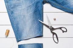 Джинсы вырезывания с портноем scissors для того чтобы сделать шорты на деревянном t Стоковые Изображения
