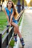 Джинсы девушки ролика нося сидя на загородке утюга Стоковая Фотография RF