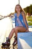 Джинсы девушки ролика нося сидя на стенде Стоковые Фото