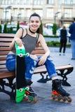 Джинсы девушки ролика нося сидя на стенде outdoors Стоковые Фото