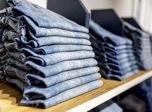 Джинсы или брюки на полке в одежде бутика и appar джинсовой ткани стоковое изображение rf