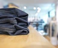 Джинсы или брюки на полке в одежде бутика и appar джинсовой ткани стоковое изображение
