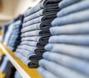 Джинсы или брюки на полке в одежде бутика и appar джинсовой ткани стоковая фотография
