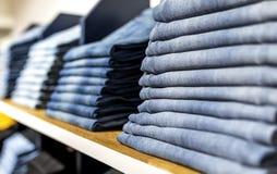 Джинсы или брюки на полке в одежде бутика и appar джинсовой ткани стоковое фото