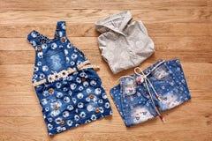 Джинсы, куртка и джинсовая ткань ` s детей одевают на деревянной предпосылке Стоковая Фотография