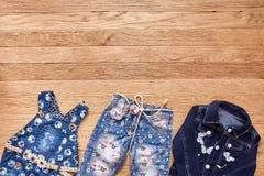 Джинсы, куртка и джинсовая ткань ` s детей одевают на деревянной предпосылке Стоковые Фотографии RF
