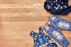 Джинсы, куртка и джинсовая ткань ` s детей одевают на деревянной предпосылке Стоковые Изображения RF