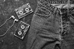 Джинсы, магнитофонная кассета, план наушников на черноте Стоковое Изображение RF