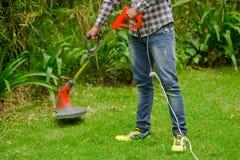 Джинсы молодого работника нося и длинная рубашка рукава и использование травы вырезывания косилки триммера лужайки в запачканной  Стоковое фото RF