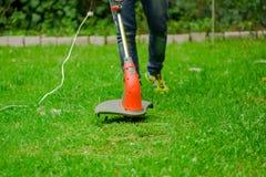 Джинсы молодого работника нося и использование травы вырезывания косилки триммера лужайки в запачканной предпосылке природы Стоковая Фотография RF