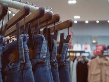Джинсы на вешалках в магазине моды Концепция на вскользь одеждах и Стоковые Изображения RF