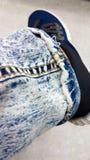 Джинсы ноги джинсовой ткани длинные с желтым stitchingon нога человека с sh Стоковые Фотографии RF