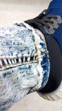 Джинсы ноги джинсовой ткани длинные с желтым stitchingon нога человека с sh Стоковое Изображение