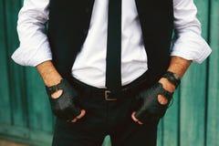 Джинсы, перчатки и жилет стильного человека нося представляя на предпосылке грубой деревянной стены, минималистской городской оде Стоковое фото RF