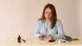 Диабетик девушки конца-вверх изменяет ланцет на ручке glucometer видеоматериал
