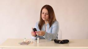 Диабетическая девушка проверяя уровень сахара в крови с glucometer дома сток-видео