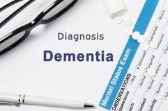 Диагноз слабоумия Результаты умственного экзамена состояния, контейнера с крошенными таблетками с диагнозом Dementi надписи психи стоковое фото
