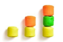 Диаграмма в виде вертикальных полос сделанная красочных частей моделируя изолированную глину на белой предпосылке Стоковое Фото