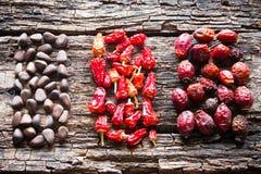 Диаграмма гаек сосны, сухого красного перца и dogrose на деревянной предпосылке Стоковая Фотография RF