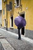 Диаграмма девушки в брюках закрыла ультрафиолетовый свет цвета зонтика против желтых домов на старой итальянской улице Vert Стоковое Изображение