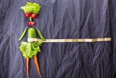 Диаграмма девушки с овощами на черной бумажной предпосылке Потеря веса и здоровый образ жизни С космосом для текста стоковое изображение