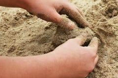 Диаграмма песка в форме сердца с руками ребенка стоковые фото