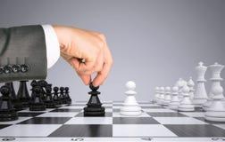 Диаграмма пешки руки бизнесмена касающая на шахмат Стоковое Изображение