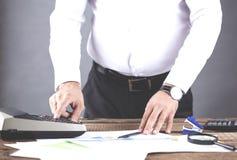 Диаграмма руки человека с калькулятором на таблице стоковое фото