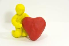 Диаграмма человек пластилина держа сердце Стоковые Изображения RF