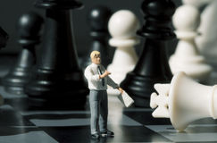 Диаграммы бизнесмена и шахмат на доске игры Играть шахмат с миниатюрным фото макроса куклы Стоковые Фотографии RF