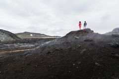 Диаграммы женщины и человека стоя в поле лавы вулкана Krafla вокруг горного пика Leirhnjukur, Исландии стоковые фото
