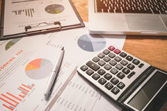 Диаграммы и диаграммы дела на деревянном столе с калькулятором, c Стоковое Изображение RF
