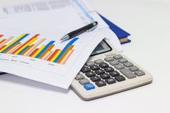 Диаграммы и ручка бумаги дела с диаграммами сообщают, калькулятор на столе финансового планирования стоковое изображение