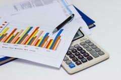 Диаграммы и ручка бумаги дела с диаграммами сообщают, калькулятор на столе финансового планирования стоковые фото